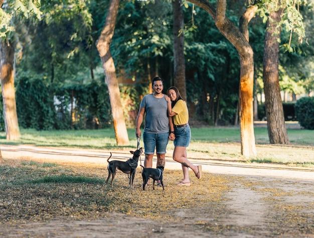 Пара позирует со своими двумя собаками в парке. счастливая пара, стоя с летней одеждой в солнечный день в парке со своими двумя щенками.