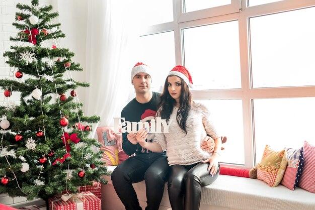 クリスマススタジオで「家族」という言葉でポーズをとるカップル