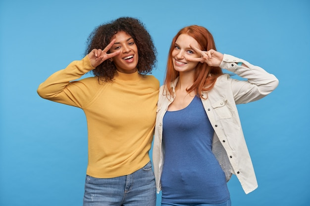 Couple of positive young attractive ladies hugging each other and smiling pleasantly , raising hands with victory gesture to their faces while posing over blue wall
