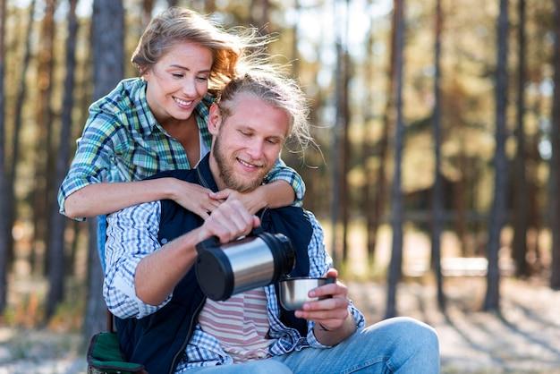 Пара наливает кофе из термоса