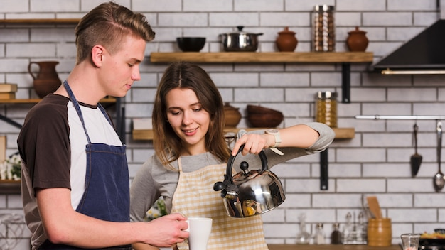 Couple pouring tea in kitchen