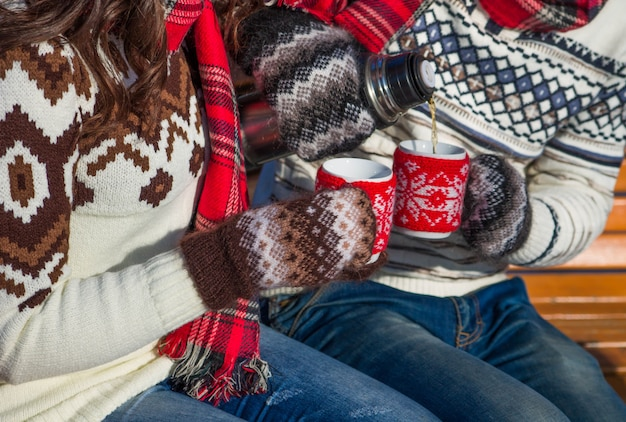 Couple pours hot tea out of thermos in winter forest