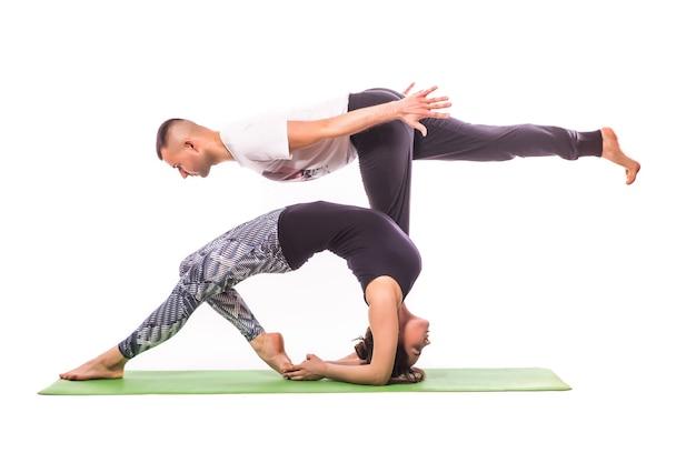 白いスタジオでアクロヨガを練習しているカップル。アクロヨガのコンセプト。ペアヨガ。ヨガの柔軟性クラスのトレーニング
