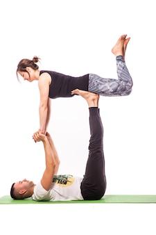 Couple practicing acro yoga in white studio. acro yoga concept. pair yoga. yoga flexibility class workout