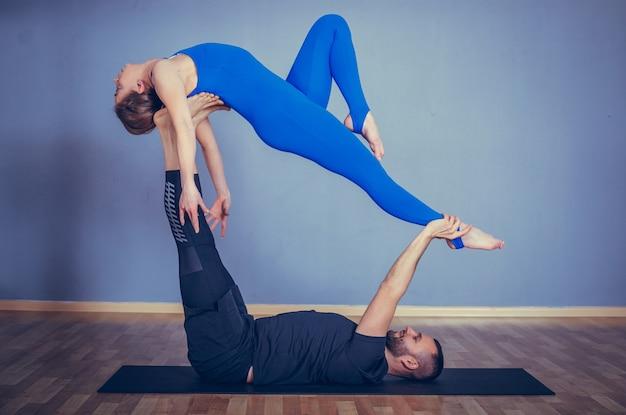 함께 acroyoga 연습 커플입니다. 흰색 스튜디오에서 acro 요가 연습하는 커플.