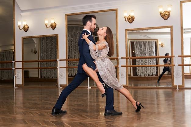 거울에 비친 넓은 빈 홀에서 탱고 춤을 연습하는 커플