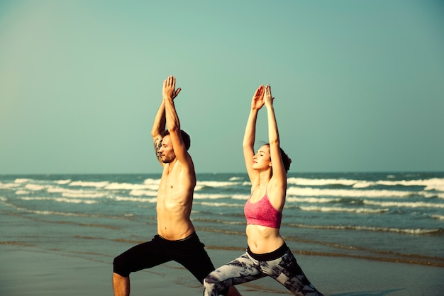 Couple practicing yoga at the beach