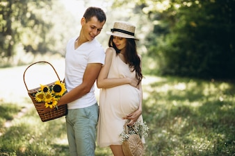 Couple pregnant, having picnic in park
