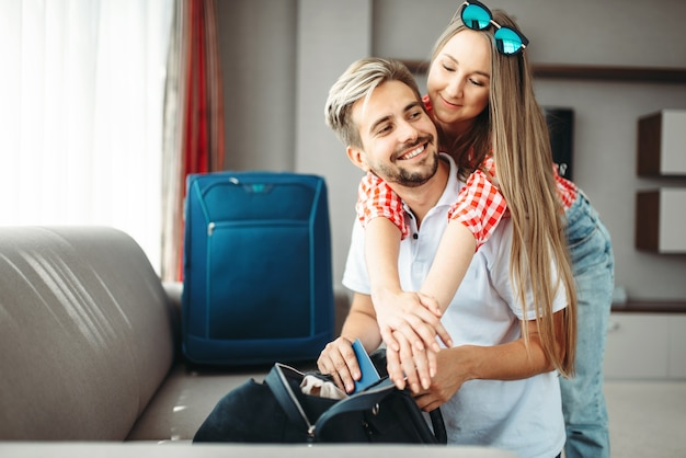 カップルは休暇のためにバッグとパスポートを準備します