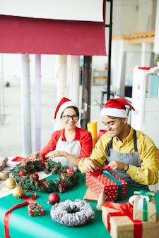 Пара готовит рождественские украшения и упаковывает подарки