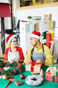 Couple preparing christmas decoration and wrapping gifts
