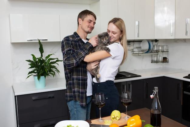 台所で夕食を準備しているカップル妻は彼女の腕に猫を抱きます