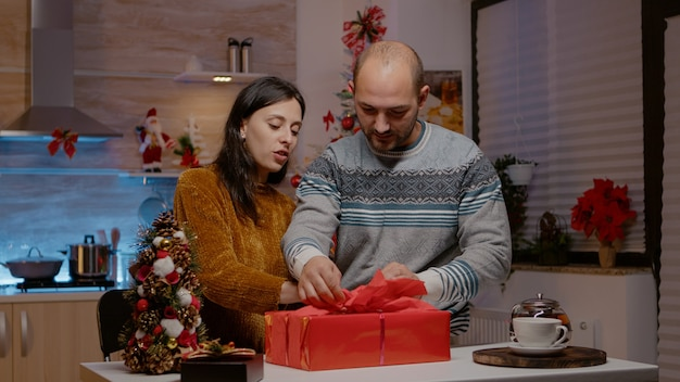 Couple preparing gift box for family on christmas eve festivity