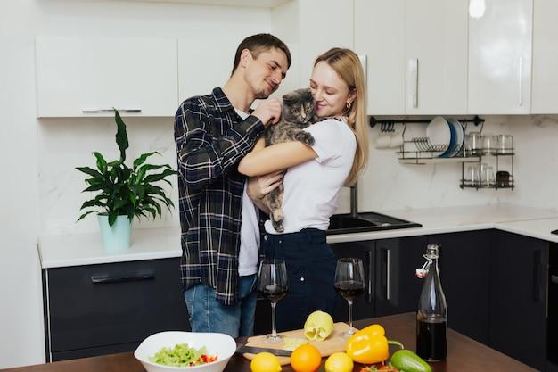 Пара готовит здоровый ужин на кухне жена держит на руках кота