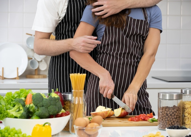 Couple preparing healthy food in kitchen.  female cutting apple fruit on chopping board, male hugging and standing behind her couple. healthy food and home cooking together concept