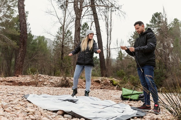 Couple preparing tent for camping