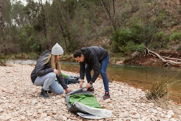 キャンプ用のテントを準備するカップル