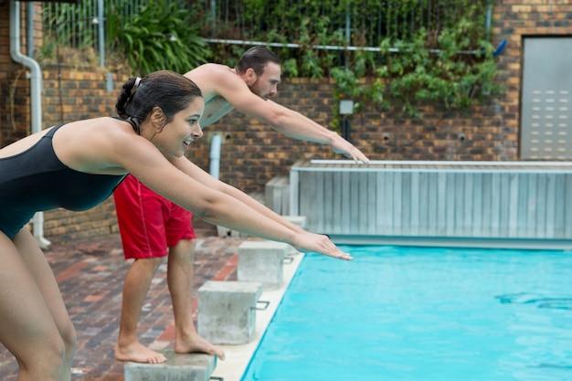 カップルがプールでダイビングする準備