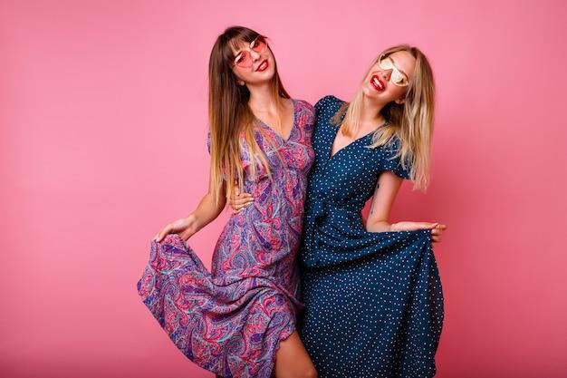 Coppia di belle amiche sorelle ragazze che si divertono insieme, indossando eleganti abiti estivi e occhiali da sole alla moda, posa al muro rosa, abbracci e sorridenti, atmosfera di festa.