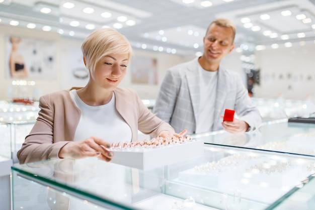 Пара покупает обручальные кольца в ювелирном магазине
