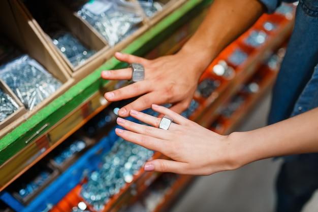 カップルは、金物屋で指輪のように指にナットを付けます。顧客は diy ショップで商品を見て