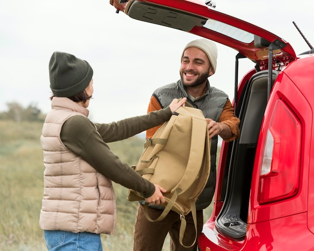 Couple putting backpacks in trunk