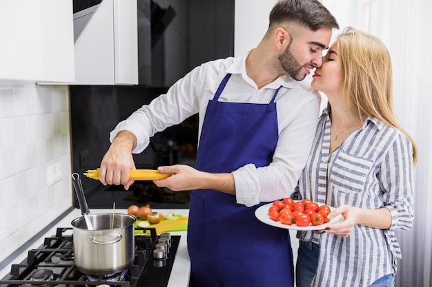 Couple putting spaghetti in pot with boiled water