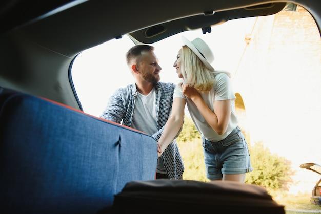 Пара кладет чемоданы в багажник автомобиля для путешествия