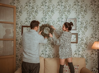 Couple putting wreath on wall