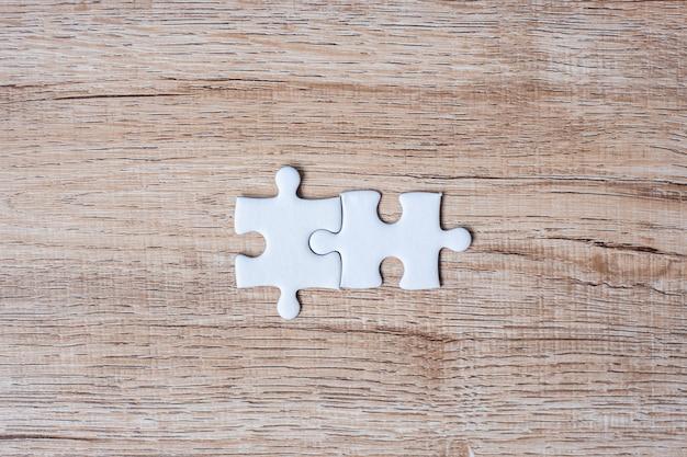 木製テーブルの上のカップルパズルのピース。ビジネスソリューション、ミッションターゲット