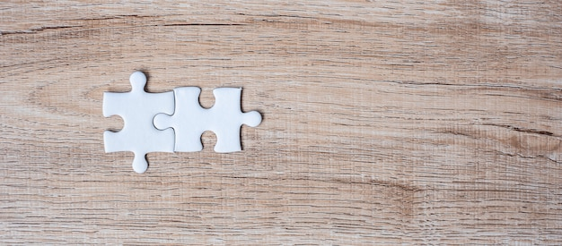 Couple puzzle pieces on wood table background. business solutions, mission target, successful, goals, cooperation, partnership and strategy