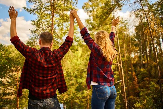 カップルが手を挙げて一緒に森でリラックス