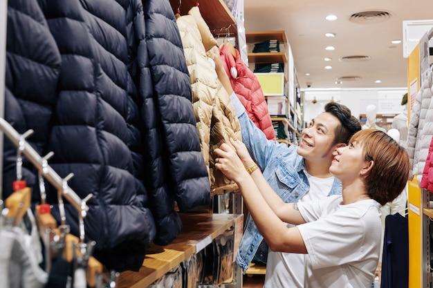 暖かい冬のジャケットに手を伸ばすカップル