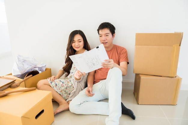Couple read blueprint for new house interior