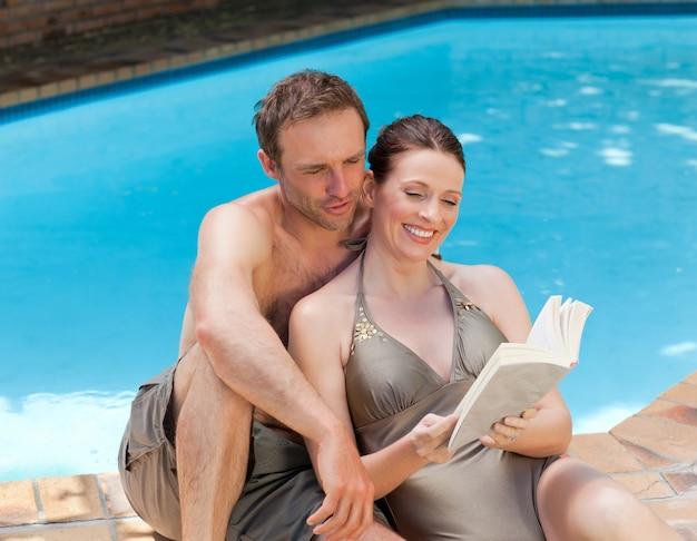 プールの横にある本を読んでいるカップル