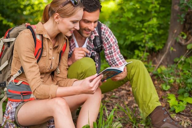 Пара, читающая книгу в лесу