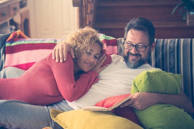 집에서 소파에서 편안한 책을 읽는 커플. 사랑하는 부부는 집에서 함께 여가 시간을 보냅니다. 집 거실에서 휴식을 취하는 아내에게 책을 읽는 행복한 남자