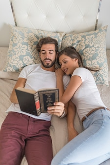 Couple reading book on bed together