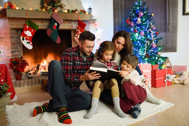 Couple reading a book with children in their living room decorated for christmas