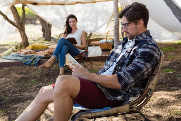Couple reading books outside tent