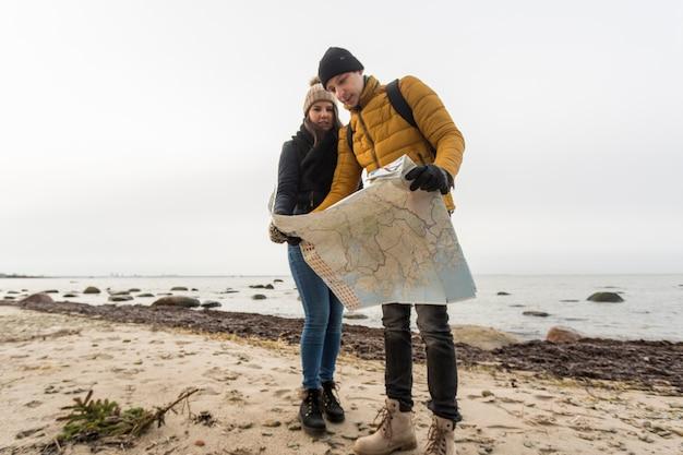 Couple reading map on coast