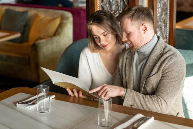 Пара, читающая меню в ресторане