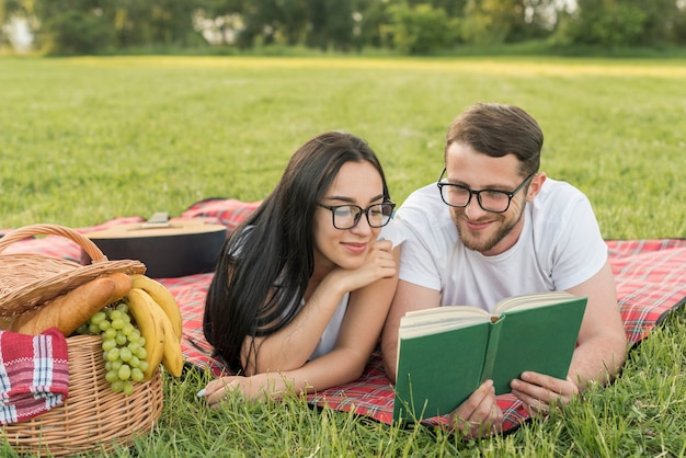 Couple reading on a picnic blanket