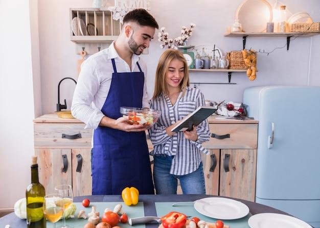 Пара, читающая книгу рецептов на кухне