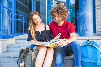 Couple reading textbook near university