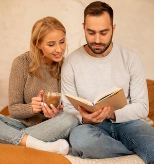 Пара, читающая вместе в помещении
