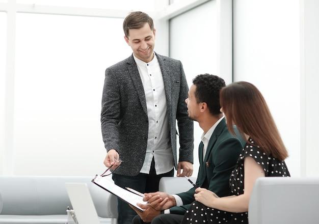 Пара читает условия контракта в офисе