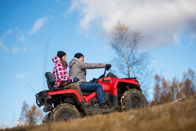 Couple on the red atv quad bike against blue sky