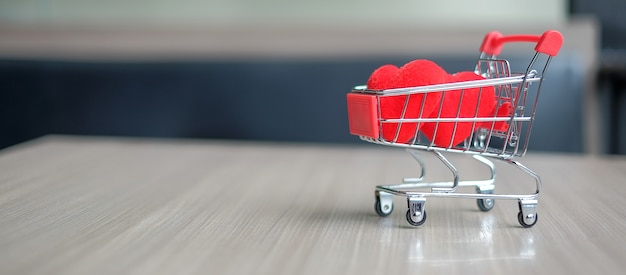 Couple red heart shape in mini shopping cart on wooden table. love and shopping concept.