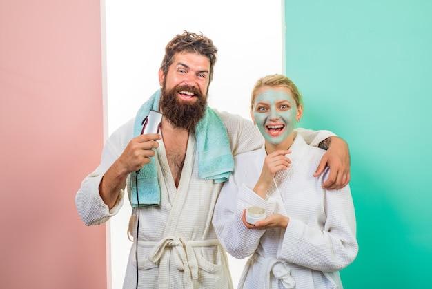 Пара. отношение. семейная жизнь. муж и жена. счастливая женщина с косметической маской для лица. бородатый мужчина с бородой стрижки электробритвой. утренние процедуры. утренняя рутина. утренние процедуры.